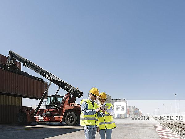 Arbeiter mit Tablette vor einem Kran mit Frachtcontainer auf einem Industriegelände