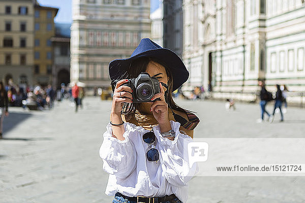 Italy  Florence  Piazza del Duomo  young tourist taking photo with camera