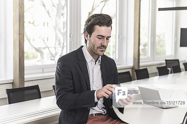 Junger Geschäftsmann sitzt im Sitzungssaal  benutzt ein Smartphone