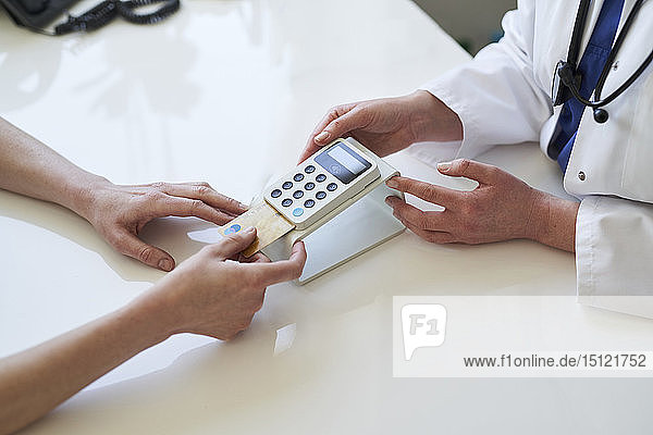 Doctor and patient with card and card reader at medical practice