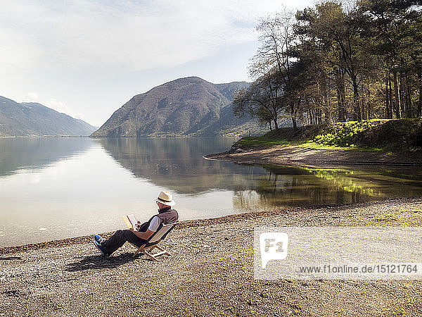 Italy  Lombardy  senior man sitting at Lake Idro using tablet