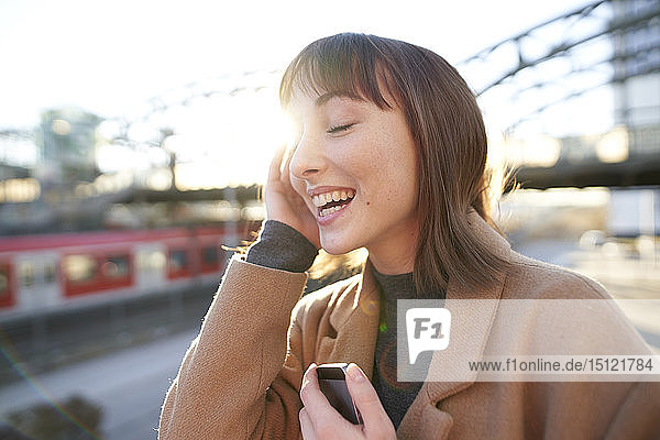 Portrait of happy young businesswoman with smartphone outdoors