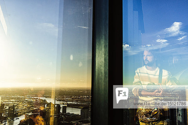 Reflection of man in glass with cityscape of Melbourne,  Victoria,  Australia