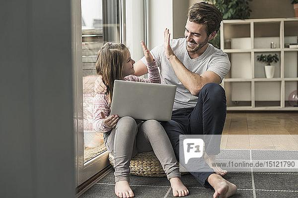 Junger Mann und kleines Mädchen surfen gemeinsam im Netz