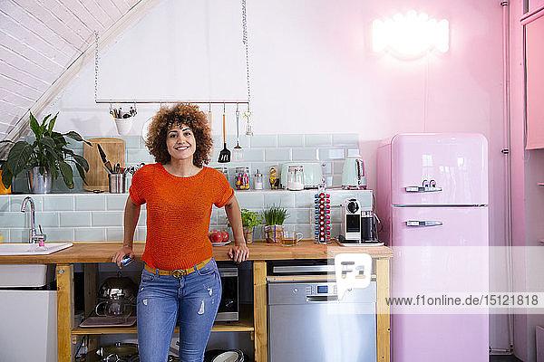 Porträt einer lächelnden Frau  die in einer Büroküche steht