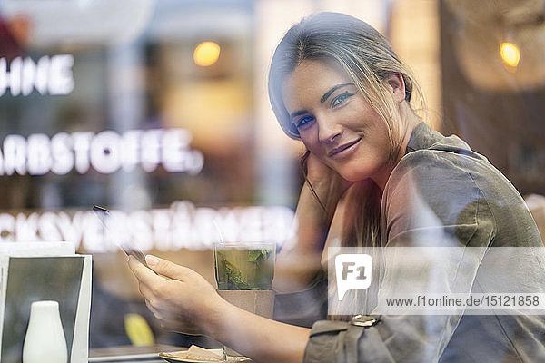 Junge Geschäftsfrau in einem Cafe  durch ein Fenster gesehen