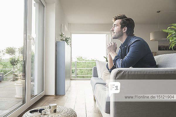Young man sitting on couch at home  looking out of window