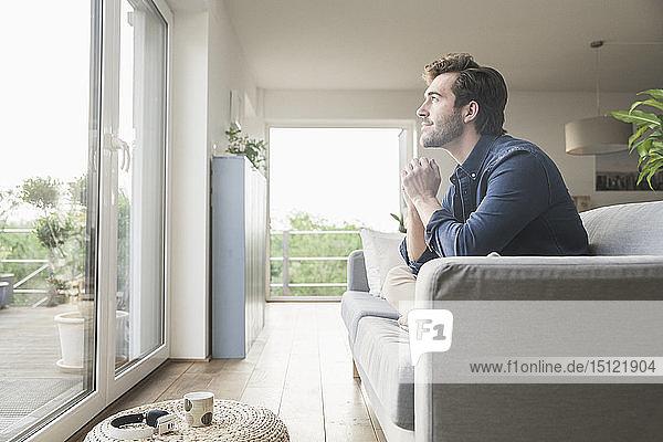 Junger Mann sitzt zu Hause auf dem Sofa und schaut aus dem Fenster