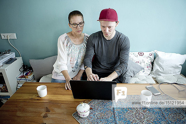 Mother and son sitting at the kitchen table  using laptop