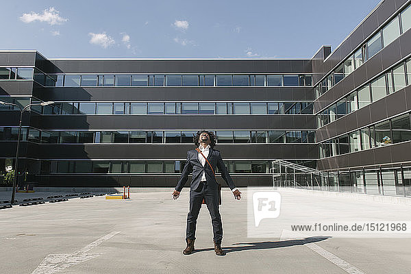 Businessman standing outside office with outstretched arms