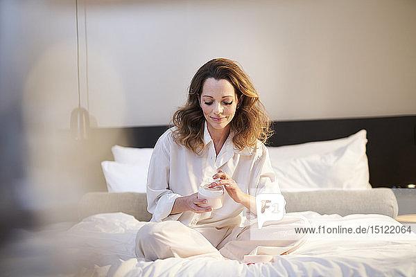 Brünette Frau sitzt auf dem Bett und trägt Schönheitscreme auf