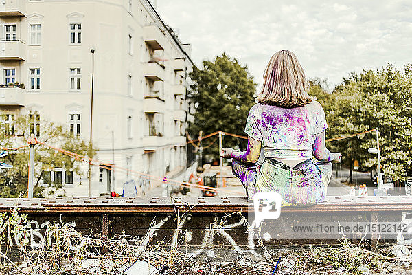 Girl with Holi colours on her clothes sitting on bridge  Germany