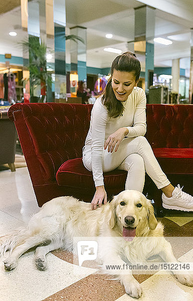 Smiling woman with dog sitting on couch in a vintage shop