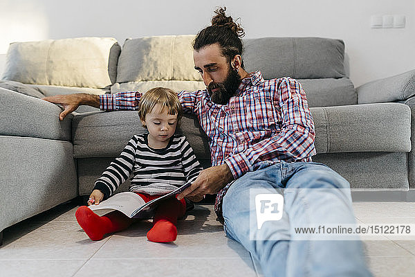 Father and little daughter sitting in the floor in the living room reading a book together