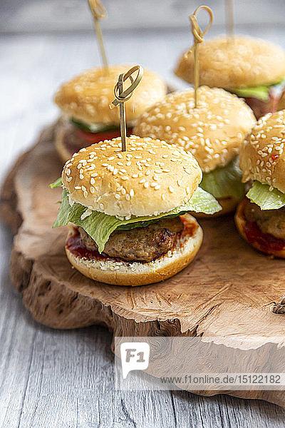 Mini-Burger mit Hackfleisch  Salat  Gurke und Tomate auf Holztablett