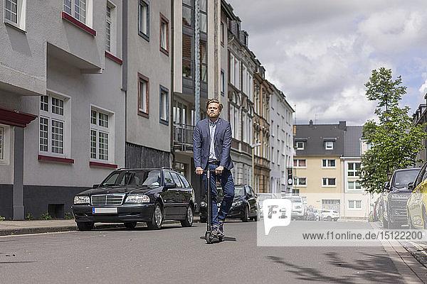 Geschäftsmann mit E-Scooter in der Stadt