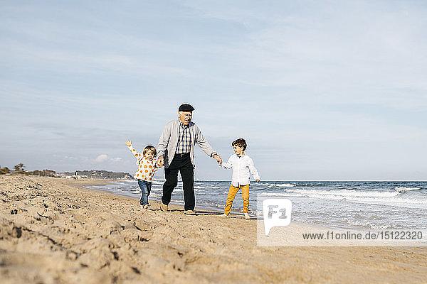 Großvater amüsiert sich mit seinen Enkelkindern am Strand