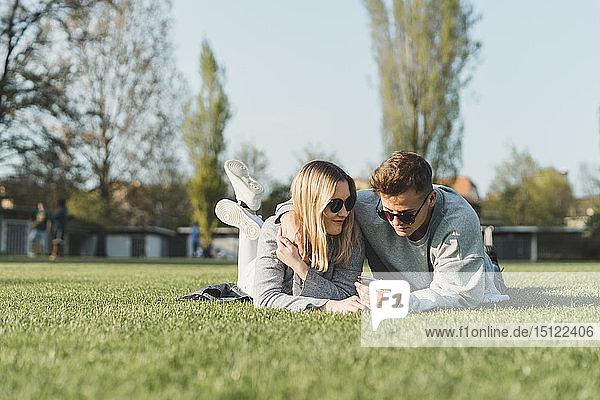 Junges Paar mit Sonnenbrille liegt auf einer Wiese und schaut auf sein Handy
