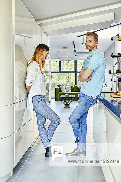 Young couple standing in kitchen  talking
