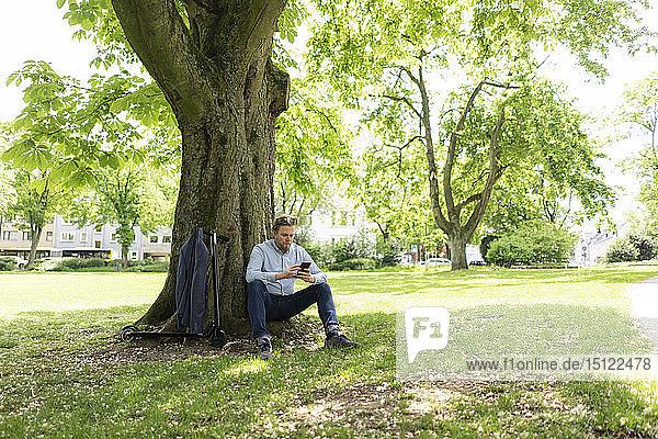 Geschäftsmann mit E-Scooter lehnt mit Smartphone an Baumstamm im Stadtpark