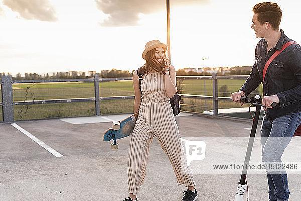 Glückliches junges Paar mit Handy  Longboard und Elektroroller auf dem Parkdeck