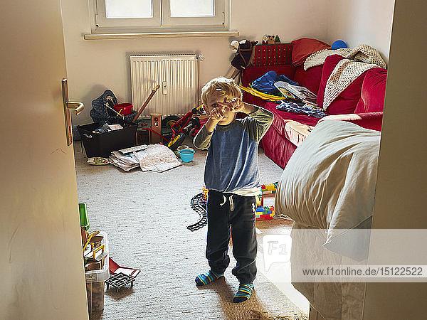 Kleiner Junge steht mit verschränkten Fingern in seinem unordentlichen Zimmergebäude