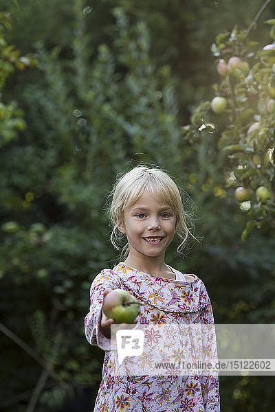 Portrait of smiling girl offering an apple