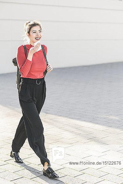 Glückliche junge Frau mit Smartphone in der Stadt