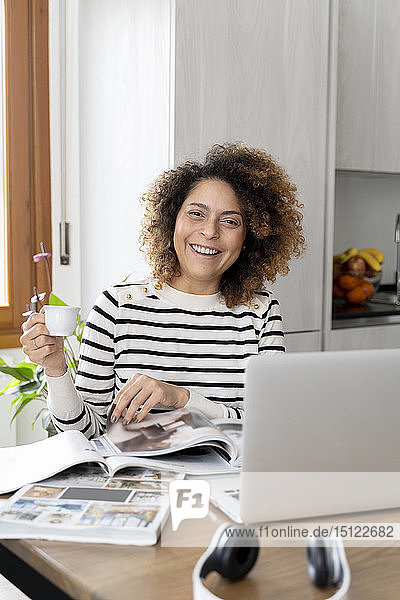 Womans reading magazines  using laptop
