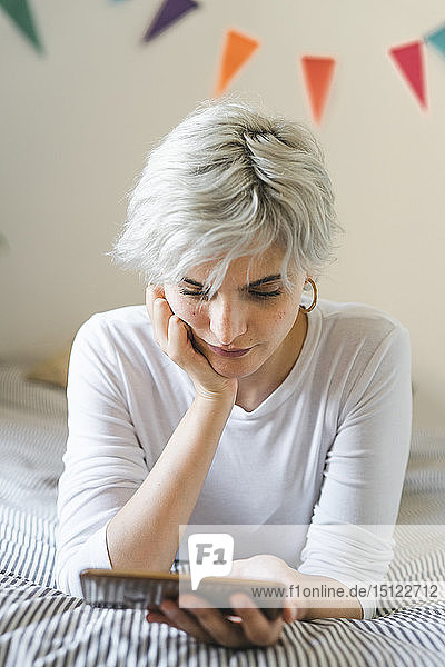 Woman using cell phone on bed at home
