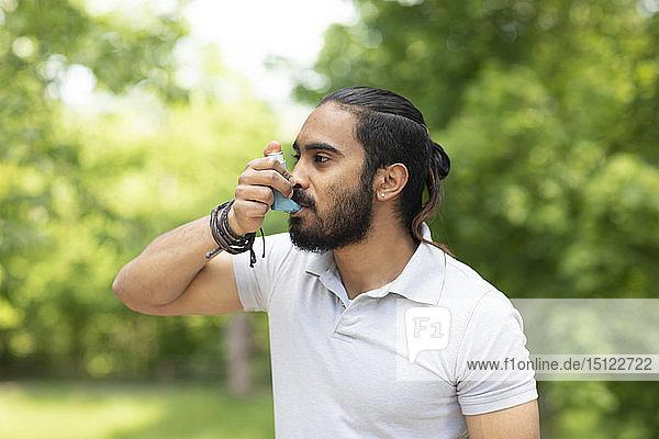 Junger Mann in der Natur mit Asthma-Inhalator