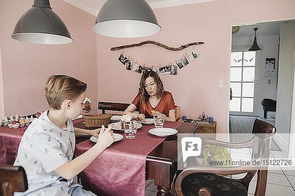 Mutter und Sohn sitzen zu Hause am Esstisch