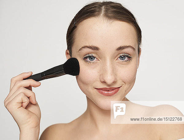 Portrait of smiling young woman with beauty brush
