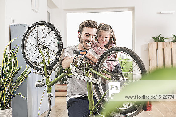 Young man and little girl repairing bicycle together