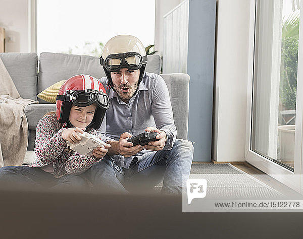 Young man and little girl wearing biker helmets  playing racing game with gaming consoles