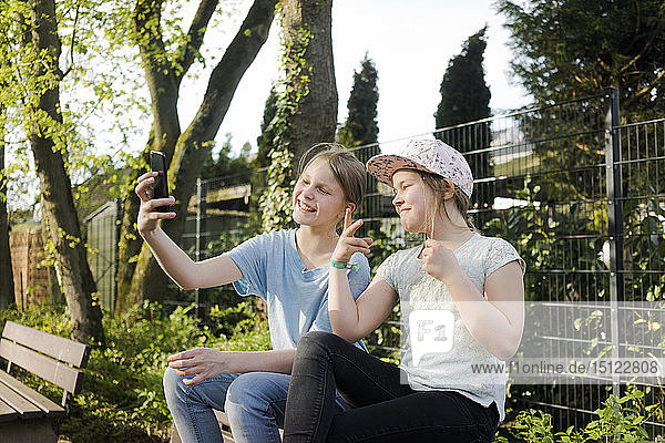 Two happy girls sitting on a park bench taking a selfie