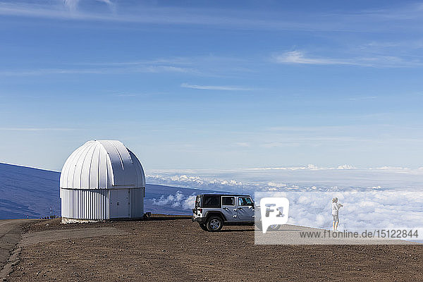 USA  Hawaii  Mauna Kea volcano  woman in front of off road vehicle at observatory