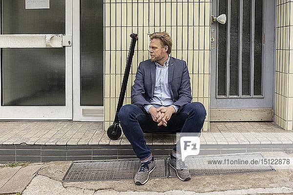 Geschäftsmann mit E-Scooter auf Stufe vor einem Haus sitzend