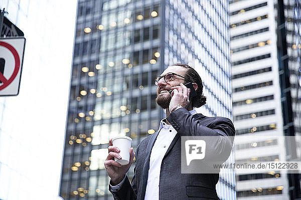 Glücklicher junger Geschäftsmann mit Kaffee zum Telefonieren  New York City  USA
