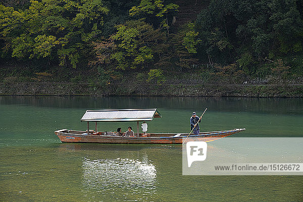 Tourists sightseeing in a small wooden boat on the Oi River in the Arashimaya region outside Kyoto  Japan  Asia