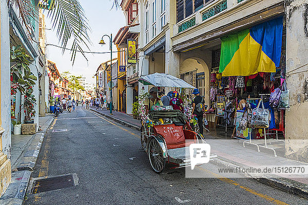 A local rickshaw (tuk tuk) driver in a colourful street scene in George Town  Penang Island  Malaysia  Southeast Asia  Asia