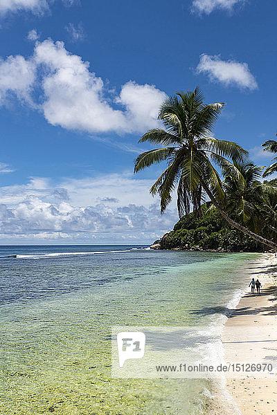 A couple walking along Anse Parnel on the southeast coast of Mahe  Seychelles  Indian Ocean  Africa