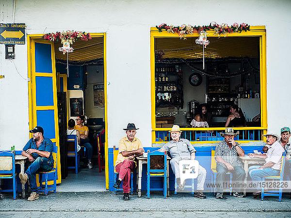 Men sit outside a bar  Jardin  Antioquia  Colombia  South America