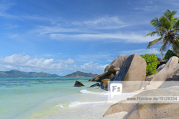 Waves swirling around large granite boulders and palm trees on Anse Source d'Argent  La Digue  Seychelles  Indian Ocean  Africa