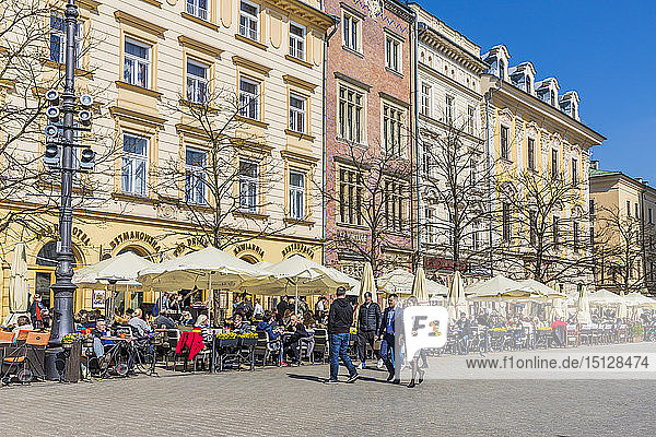 A cafe scene in the main square  Rynek Glowny  in the medieval old town  UNESCO World Heritage Site  Krakow  Poland  Europe