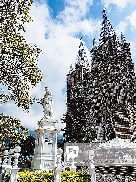 Basilica Menor de la Immaculada Concepcion faces the Parque Principal and a monument to women  Jardin  Colombia  South America