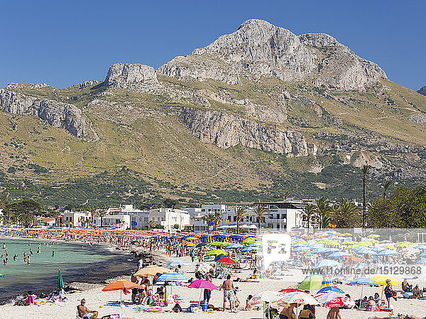 View across colourful crowded beach to the rugged slopes of Pizzo di Sella  San Vito Lo Capo  Trapani  Sicily  Italy  Mediterranean  Europe