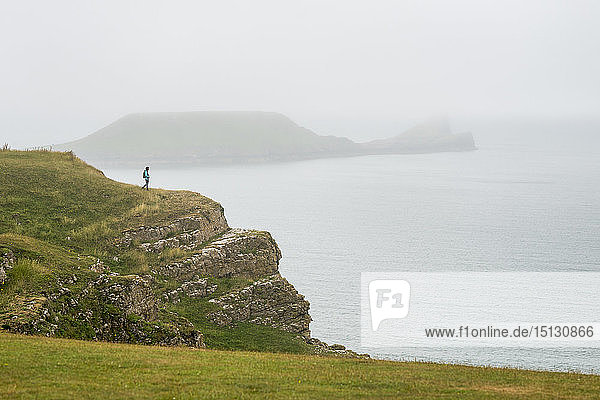 A woman looking towards Worms Head on The Gower peninsula on a misty day  Wales  United Kingdom  Europe