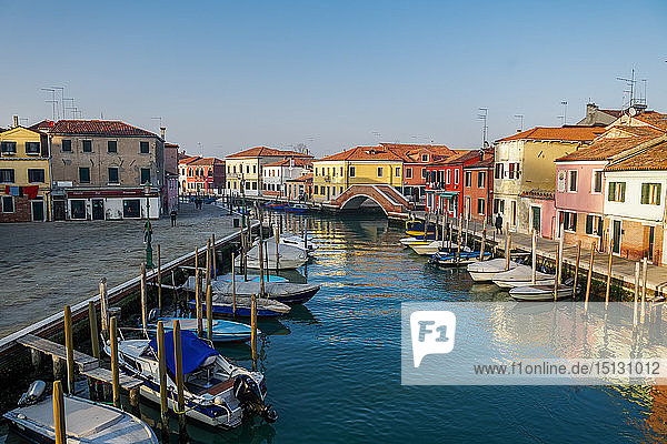 View of Ponte San Martino stone bridge over canal with colorful buildings and moored boats on wooden wharf pilings  Venice  UNESCO World Heritage Site  Veneto  Italy  Europe