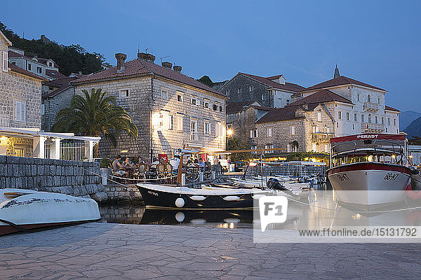 View across the illuminated harbour to waterfont mansions overlooking the Bay of Kotor  dusk  Perast  Kotor  UNESCO World Heritage Site  Montenegro  Europe